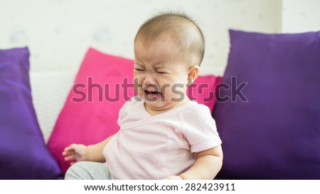 many causes of crying baby such as hungry, tried, upset and hurt from something. - stock photo