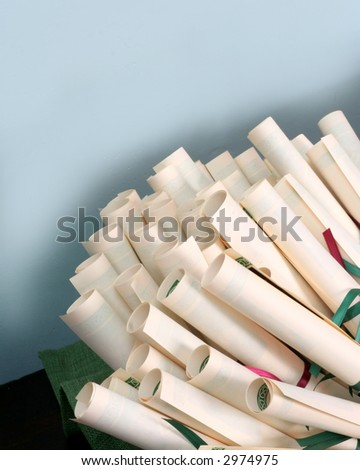 Many Certificates Rolled and Tied with Ribbon on Display with a Blue Background. - stock photo