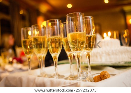 Many Champagne Glasses on a Tray with Anniversary Cake in Background - stock photo