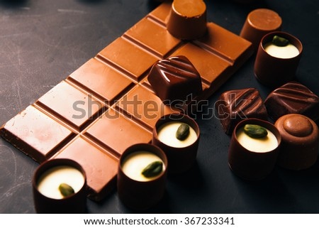 Many chocolate sweets with Pistachio on black background  - stock photo