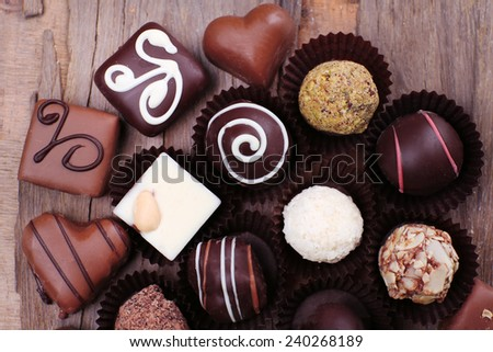 Many chocolates on wooden textured background - stock photo