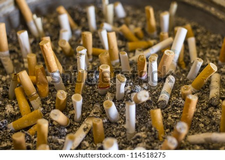 many cigarette butts in ashtray - stock photo