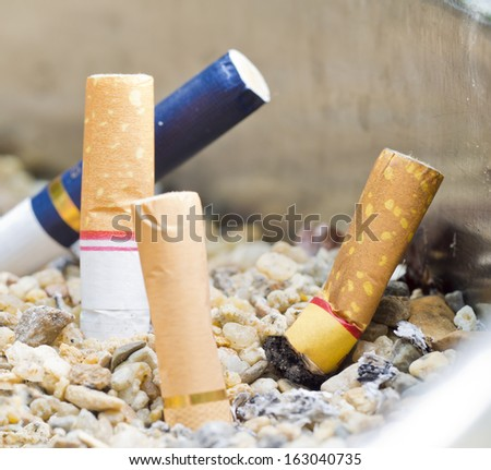 many cigarette butts in the ashtray. photo taken in the natural light. - stock photo