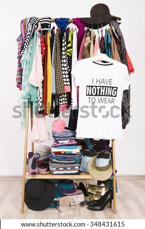 Many clothes on the rack with a t-shirt saying nothing to wear. Close up on a cluttered wardrobe with colorful clothes and accessories, many clothes and nothing to wear. - stock photo