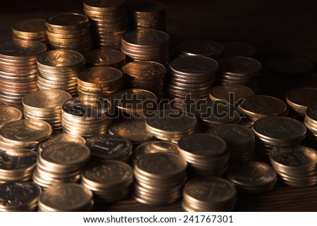 Many coins in columns on dark background - stock photo