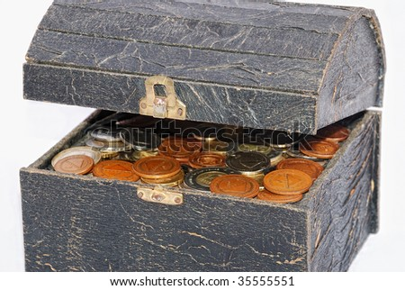 Many coins in one old chest isolated - stock photo