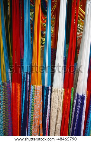 many colored hammocks hang together in the shop - stock photo