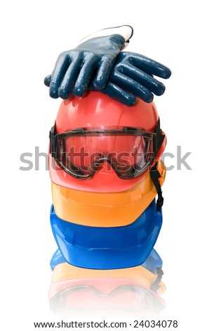 Many colored hardhats, gloves and goggles on white - stock photo
