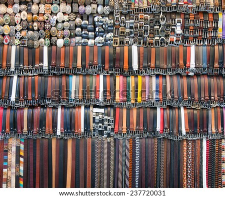 Many colored leather belts on a market.