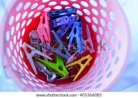 Many colorful clothespin with pink laundry basket       - stock photo
