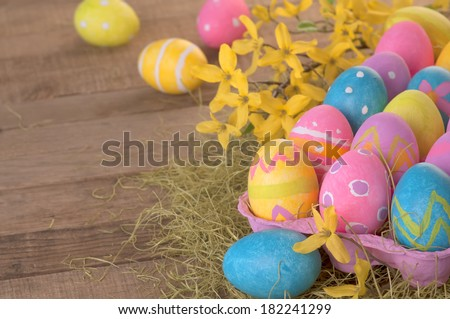Many Colorful Easter Eggs in a carton in Country Farm Style Still Life on Rustic Wood Boards as background with room or space for copy, text.  Horizontal closeup.   - stock photo