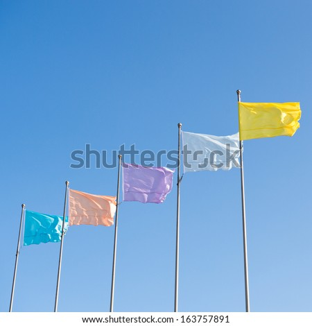 many colorful flags waving over the blue sky background. - stock photo