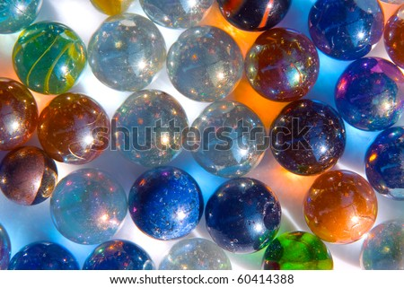 many colorful glass marbles reflecting color light on white background - stock photo