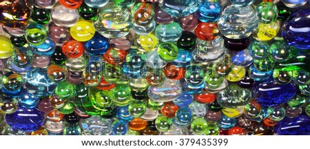 Many colorful glass marbles with smiley light reflection - stock photo