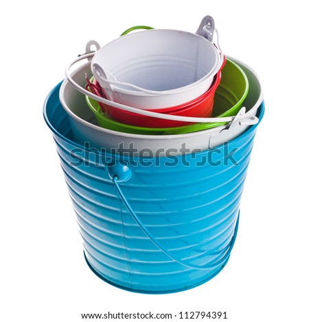 many colorful iron buckets of different sizes, folded into one another isolated on white background
