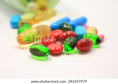 Many colorful medicines pills and capsules on white background - stock photo