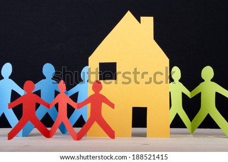 Many Colorful Paper Chain People around a House, Black Background - stock photo