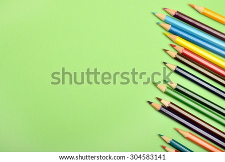 Many colorful pencil on green background - stock photo