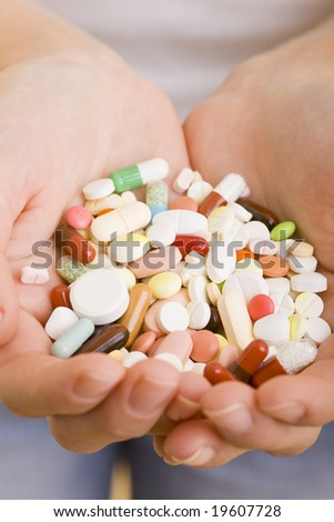 Many colorful pills a two hands - stock photo