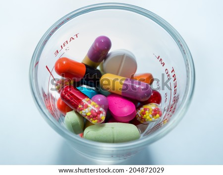 Many colorful pills in a cup of glass - stock photo
