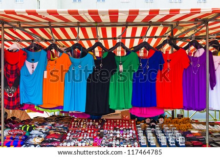 many colorful shirts for sale at a market entertainment. competition for textile trading - stock photo