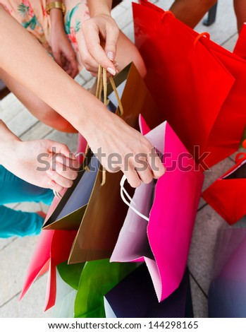 Many colorful shopping bags held by women's hands. - stock photo