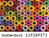 many colorful spools of thread for sewing, colorful background - stock photo