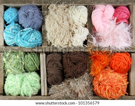 many colorful yarn balls in an aged wooden box - stock photo