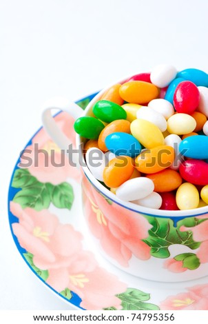 many-coloured candies into a cup saucer on light background