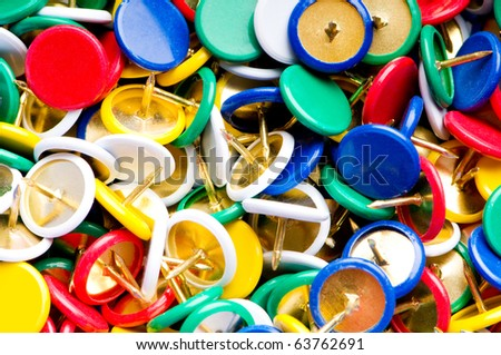 Many colourful office pins on the background
