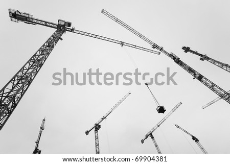 Many Construction crane against the sky and the houses under construction