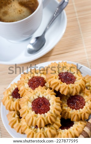 Many cookies with jelly and black coffee in cup, little teaspoon lying on saucer. Aromatic traditional beverage with delicious and decorated cookies with red jelly, vertical orientation - stock photo
