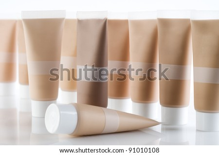 Many cosmetic tubes with creams standing on reflective background - stock photo