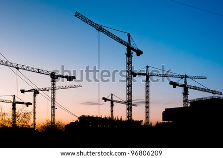 Many cranes silhouettes on clear and blue sky