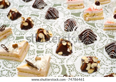 many cream sponge cakes and tapered sweets on buffet table, shallow DOF - stock photo