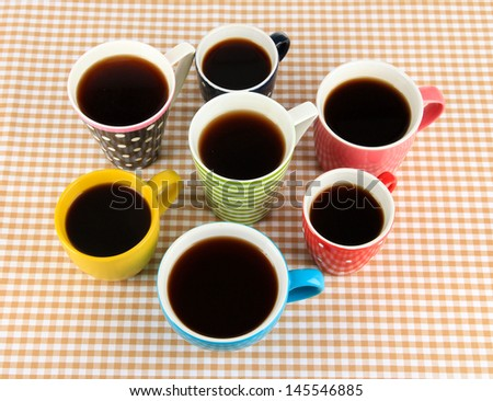 Many cups of coffee on checkered napkin - stock photo