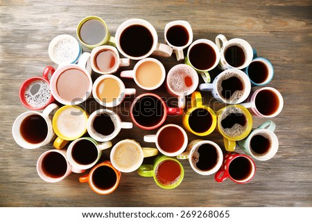 Many cups of coffee on wooden table, top view - stock photo