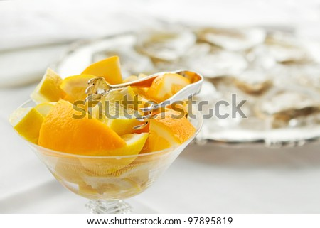 many cut orange slices in a bowl next to oysters