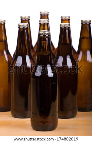 Many dark brown glass bottles full of beer on white standing on table, fresh drink in transparent glass. Object in vertical orientation, nobody in frame. - stock photo