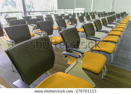 Many dark yellow chairs arranged neatly in a training room.