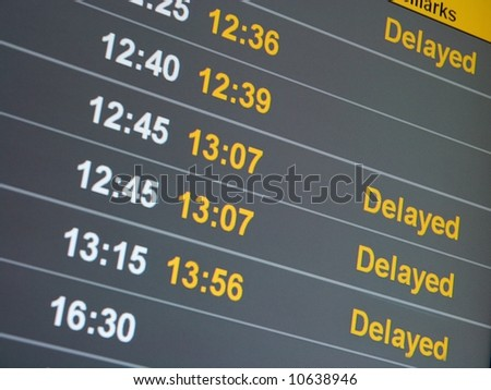 Many delayed flights on the departure table of an airport - stock photo