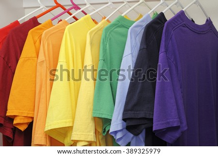 Many different colors of t-shirts hanging in a closet. A rainbow variety of ten different colors of casual mens t-shirts.