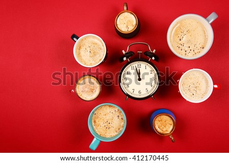 Many different cups of coffee and cappuccino and big alarm clock on red background. Too much caffeine in one day - stock photo