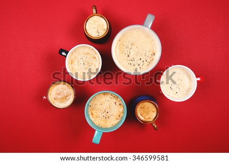 Many different cups of coffee and cappuccino on red background - stock photo