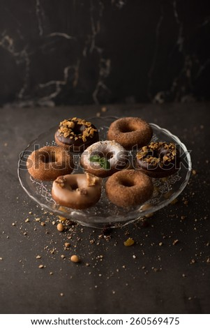 Many different donuts on glass plate on dark stone background - stock photo