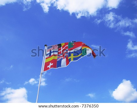 Many different European flags make one flag against a blue sky.