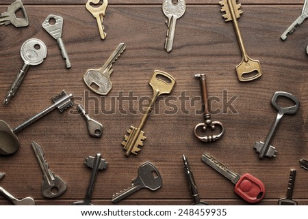 many different keys on wooden background concept - stock photo
