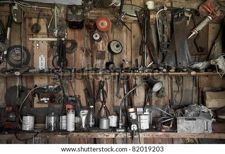 many different old tools hanging on a barn wall - stock photo