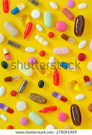 many different pills on yellow background - stock photo