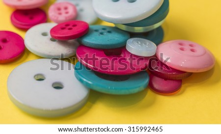 Many different vintage buttons close up isolated on a yellow background - stock photo
